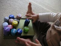 ペットボトル蓋おもちゃをならべて遊ぶ赤ちゃん