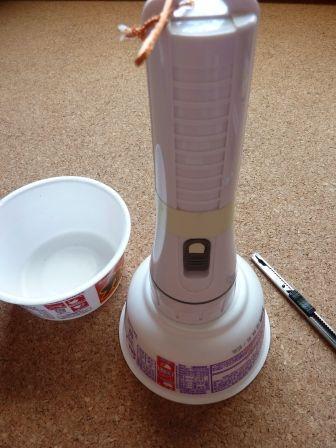 カップ麺容器の穴に懐中電灯をつっこむ