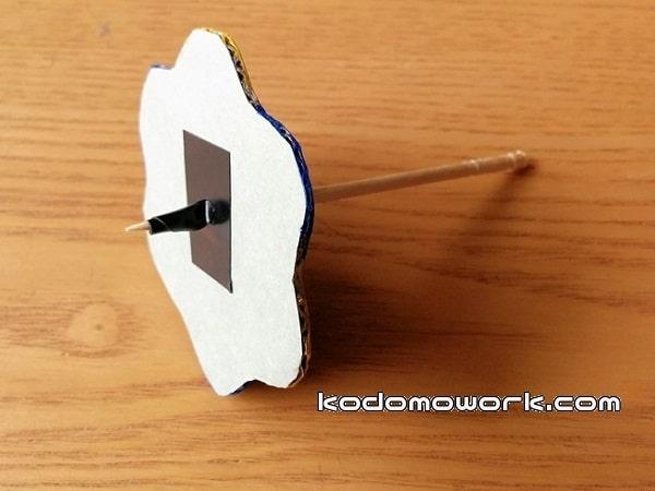 手作りこまの裏側にビニールテープをはってつまようじを固定する