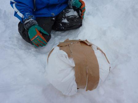 袋に雪をつめてボールにする